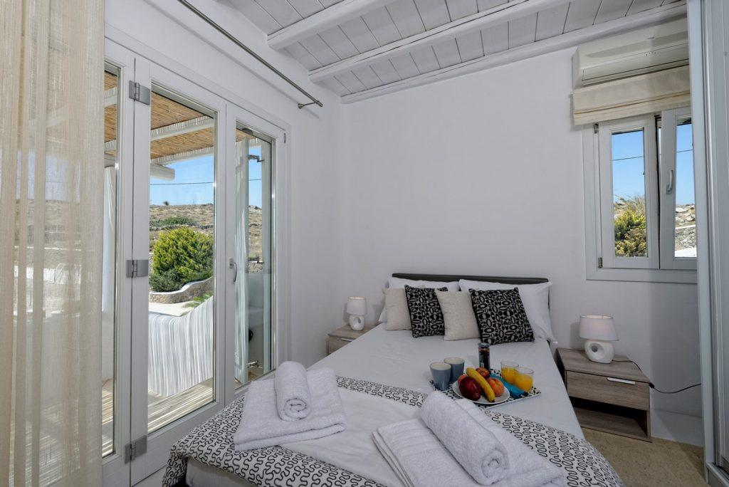 white bedroom containing king size bed two lamp nightstands