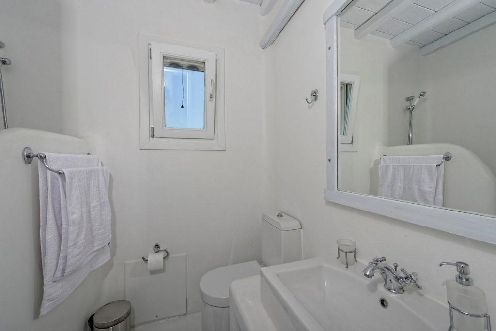 white tiled bathroom with window for natural airing