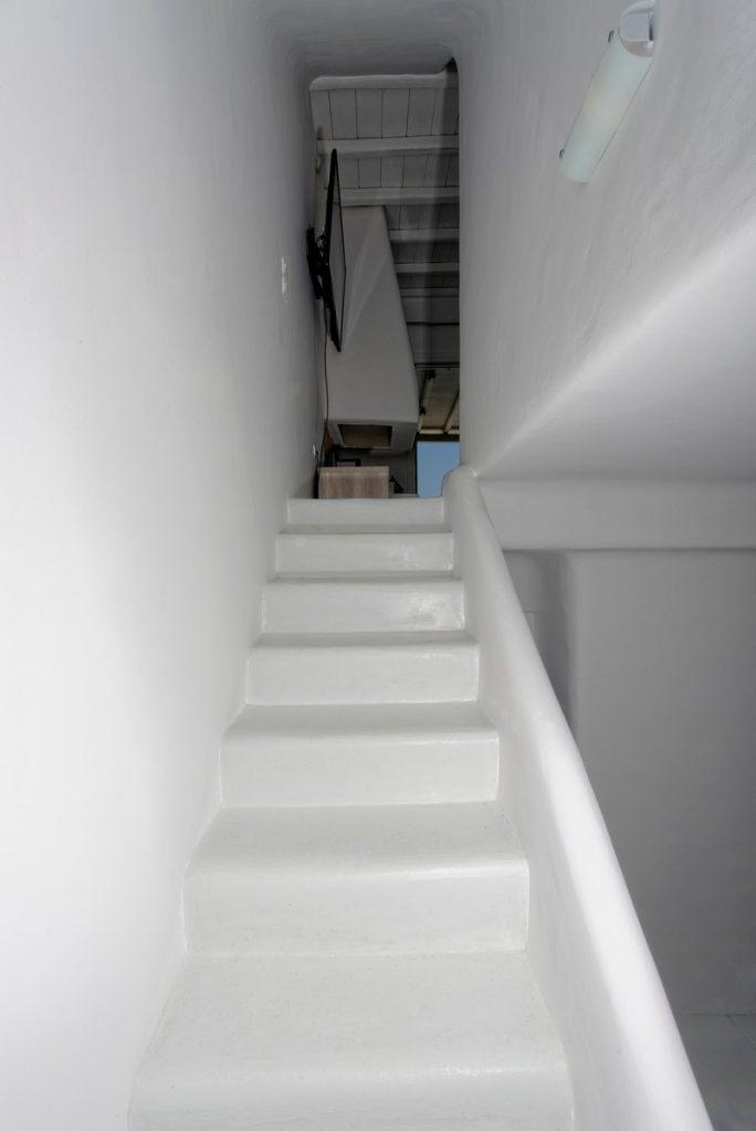 white and simply designed staircase that connects kitchen with upper floor and bedroom