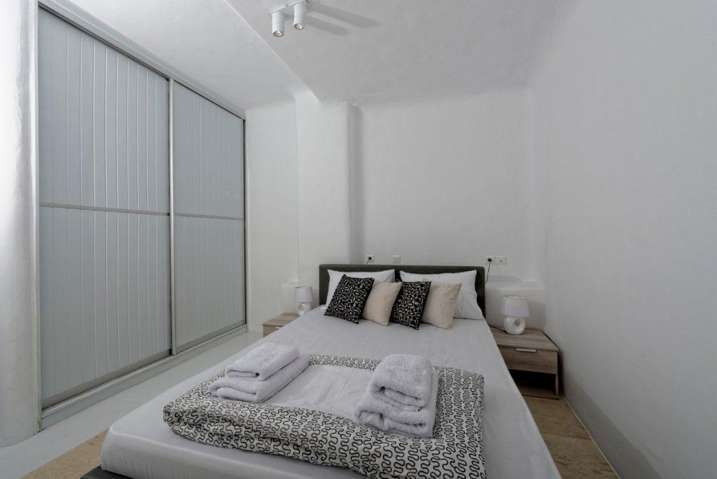 cozy and snug bedroom with closed curtains and white towels on bed