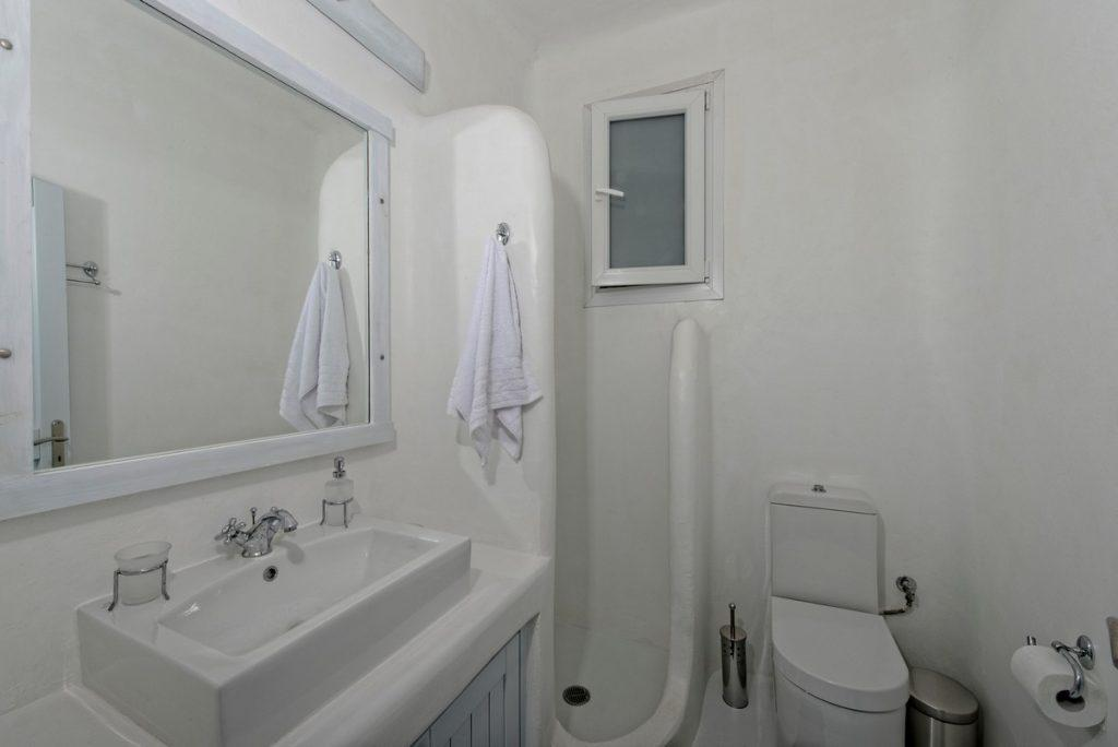 lamp illuminated bathroom with elevated sink and corner shower