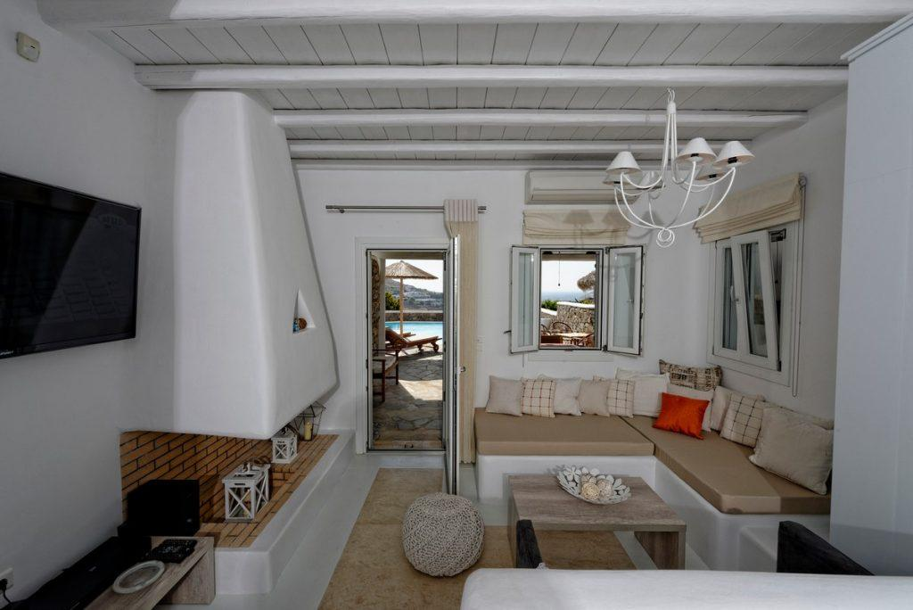 practical living space with corner comfortable sofa loads of pillows and white chandelier