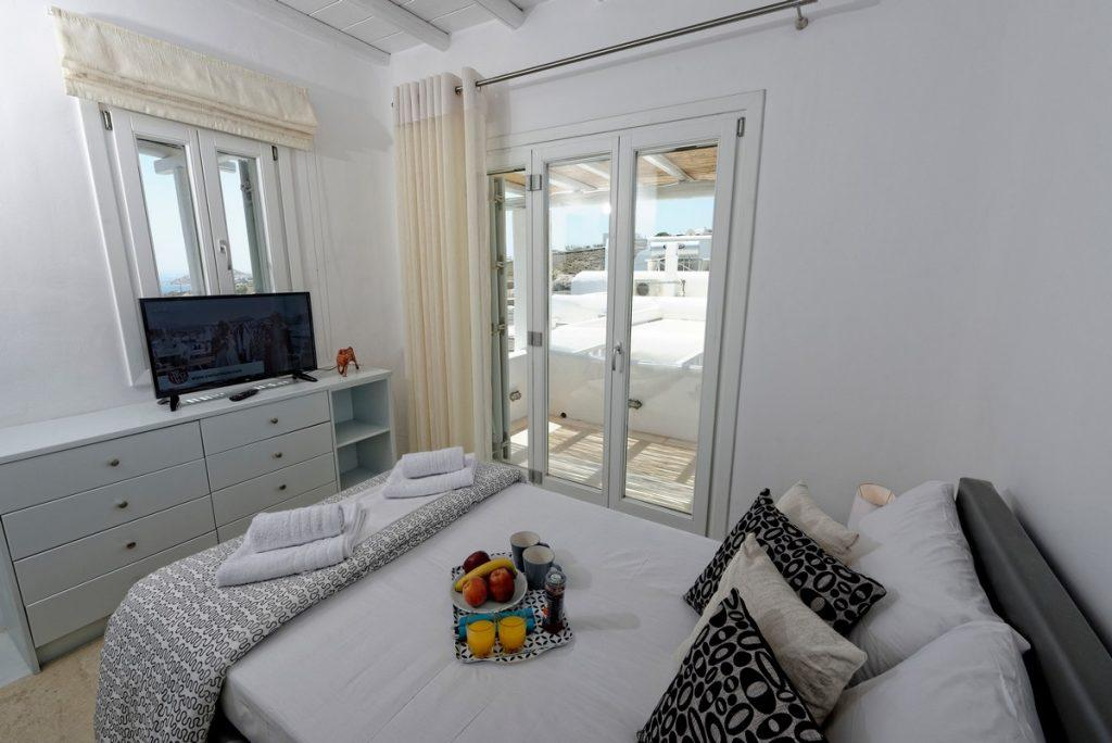 beautifully lit bedroom with TV cozy bed and soft pillows for relaxing
