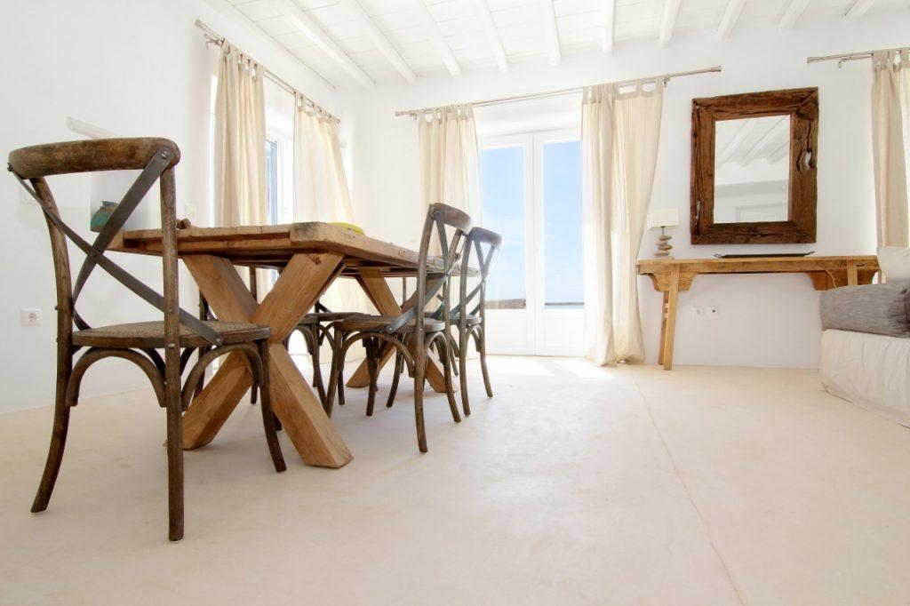 dining room with large windows that provide daylight and cream curtains that contribute to a soothing atmosphere