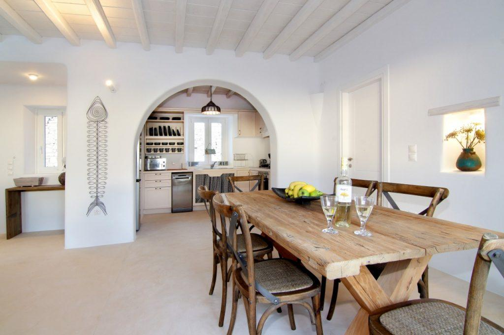 enjoying fresh fruit and wine in the spacious white-walled dining room with wooden table