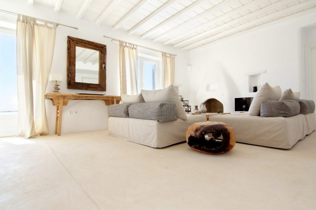 white walls living room with large windows that provide daylight and comfortable furniture