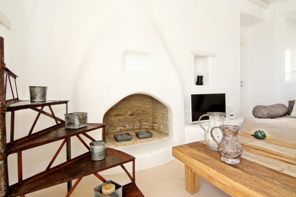 room with a brick fireplace and decorative candles that contribute to comfort