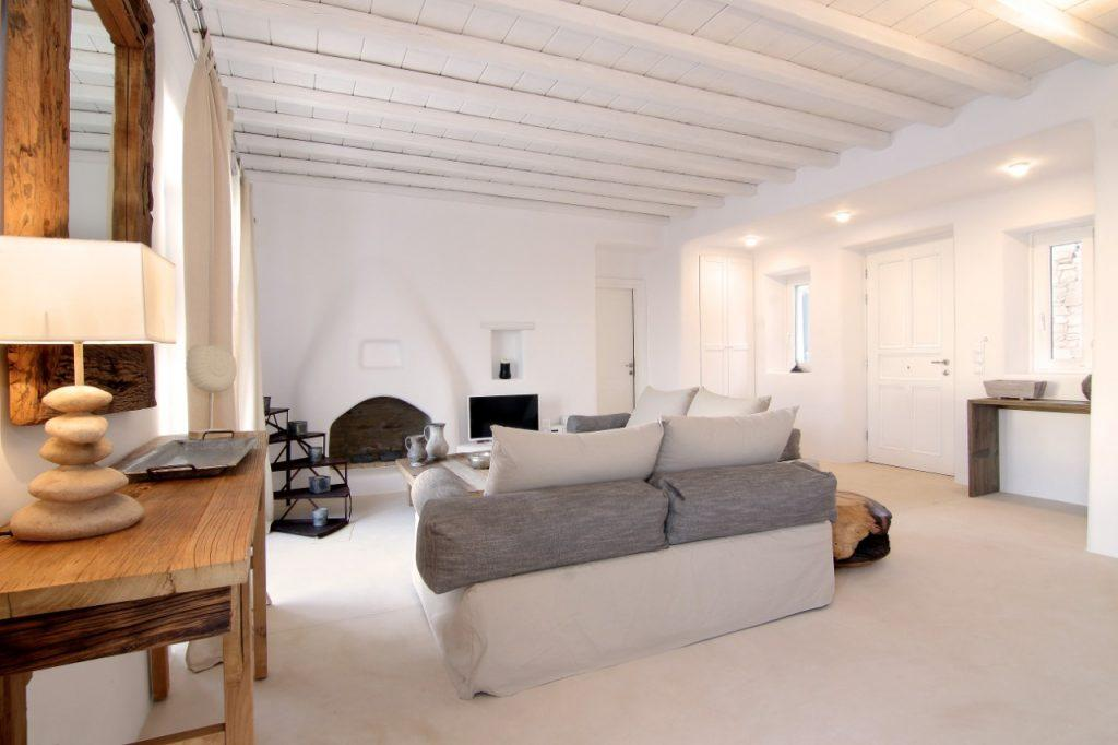 comfortable furniture in a white room with wooden details and a lamp that decorates the space