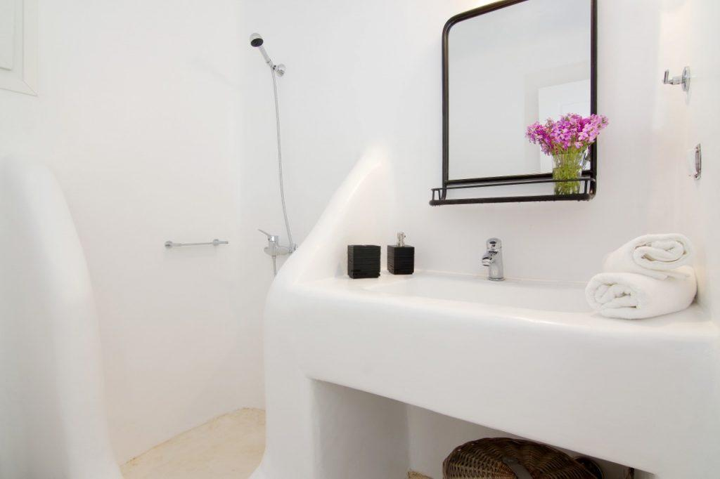 bathroom with white walls with a mirror and a decorative bouquet of pink flowers