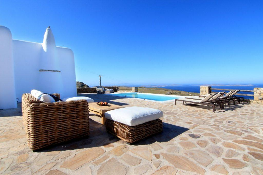view of the calm blue sea from the pool in the courtyard of the villa