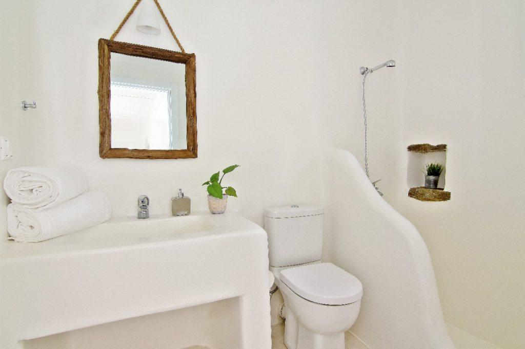bathroom with white walls and sink equipped with all necessary things