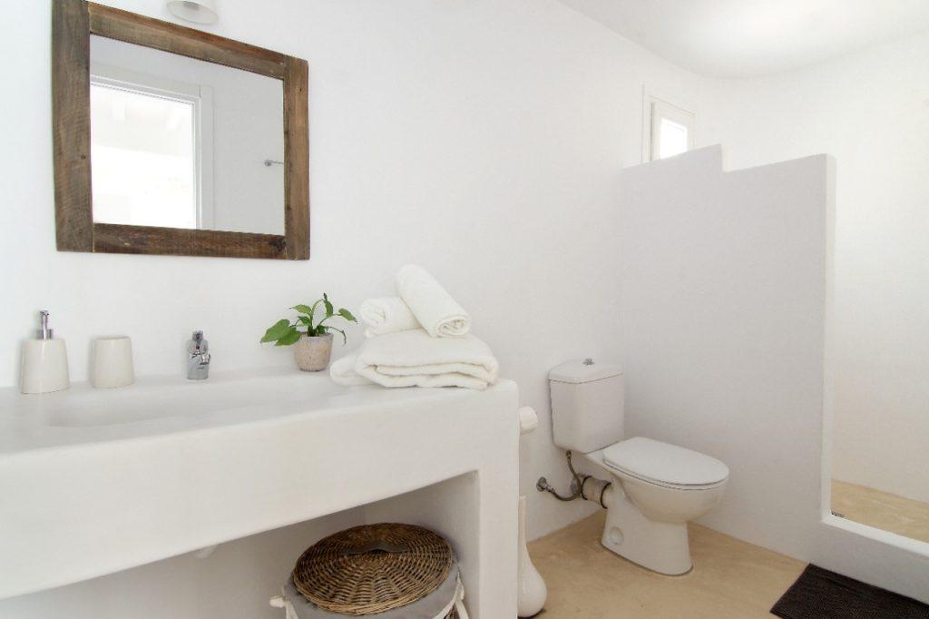 white bathroom walls and a sink with decorative green flowers