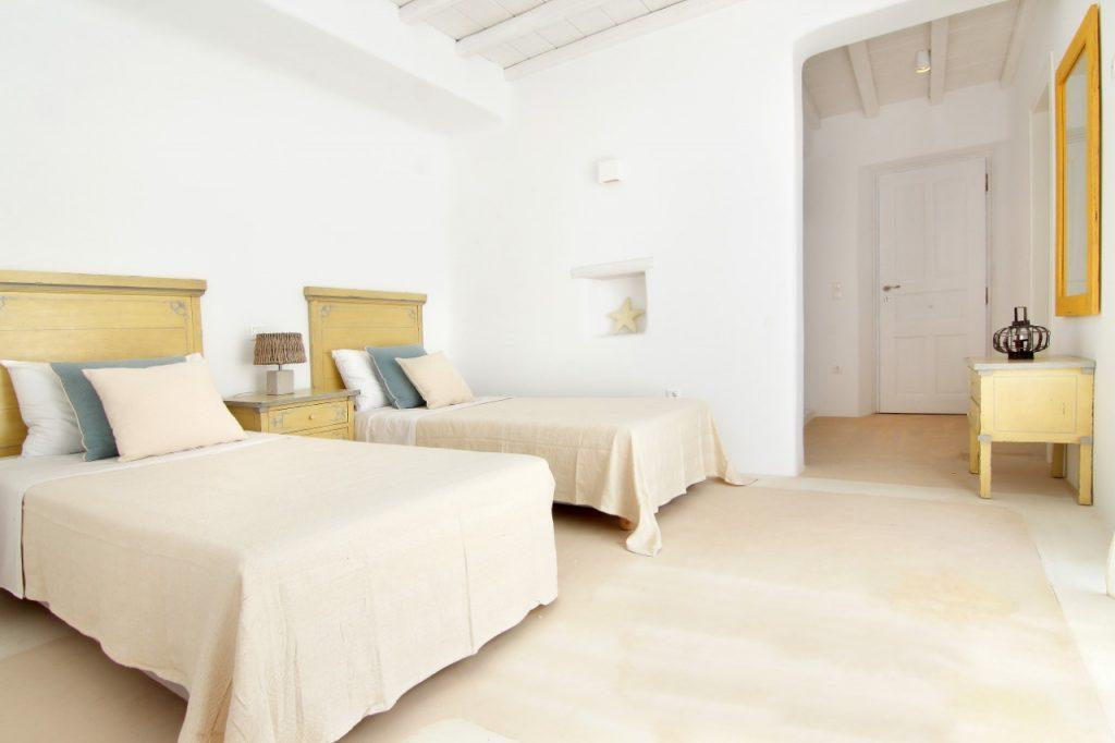 bedroom with white walls and two beds with pink bedspreads