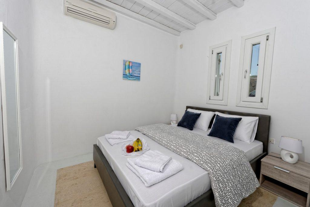 white walls of the room with gray bed and soft blue pillows ideal for sleeping