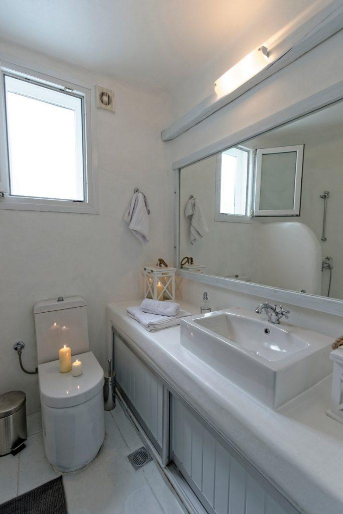 bathroom in white tone with a large mirror decorated with candles that contribute to the enjoyment of bathing
