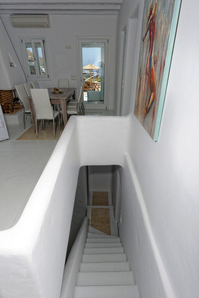white hallway walls with steps in the same tone and a vivid picture