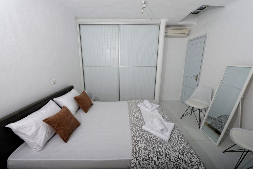 bedroom in white tone with large mirror and wardrobe