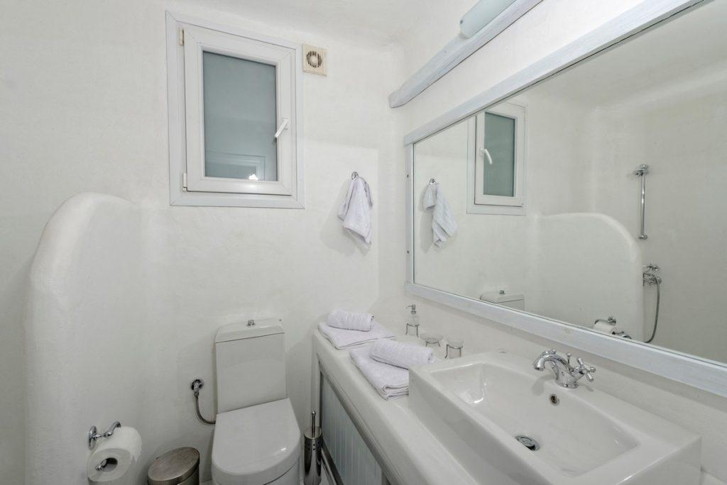 bathroom in white tone with large mirror and sink