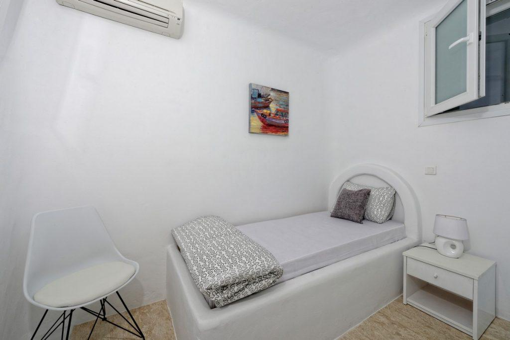white walls of the room with a comfortable bed and a modern chair in the corner