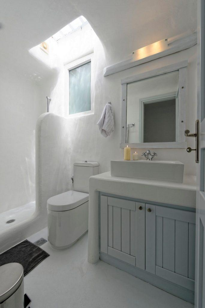 bathroom with shower and sink decorated with white scented candles for a better atmosphere