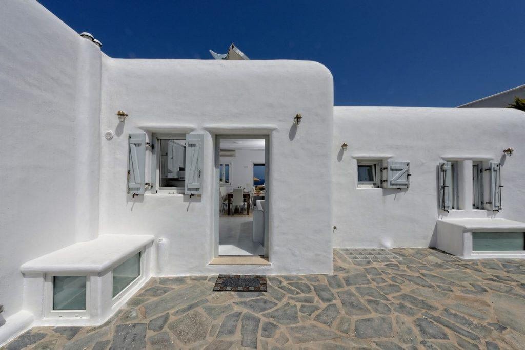 white villa with wooden windows in the same tone and a stone floor