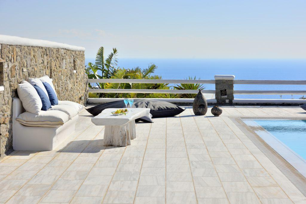 view of the bright blue sea from the comfortable garden furniture