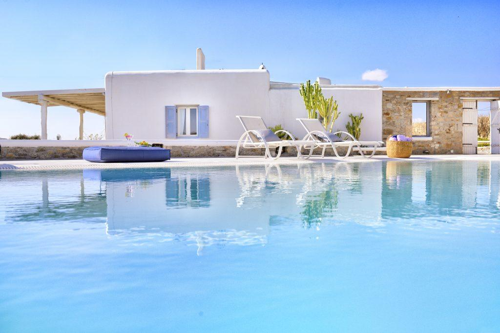 view of a white luxury villa and a beautiful garden with a swimming pool ideal for a summer vacation