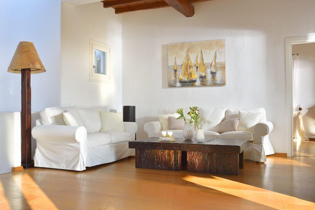 oom with comfortable white furniture and a wooden table an ideal place to relax