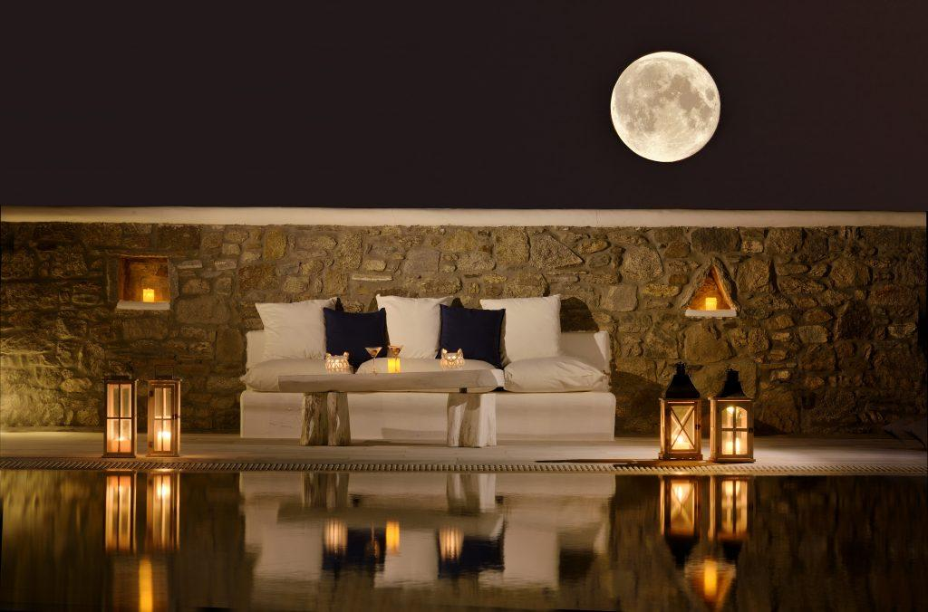 view of the starry sky and a full moon from the pool lit by candles that contribute to the romantic atmosphere