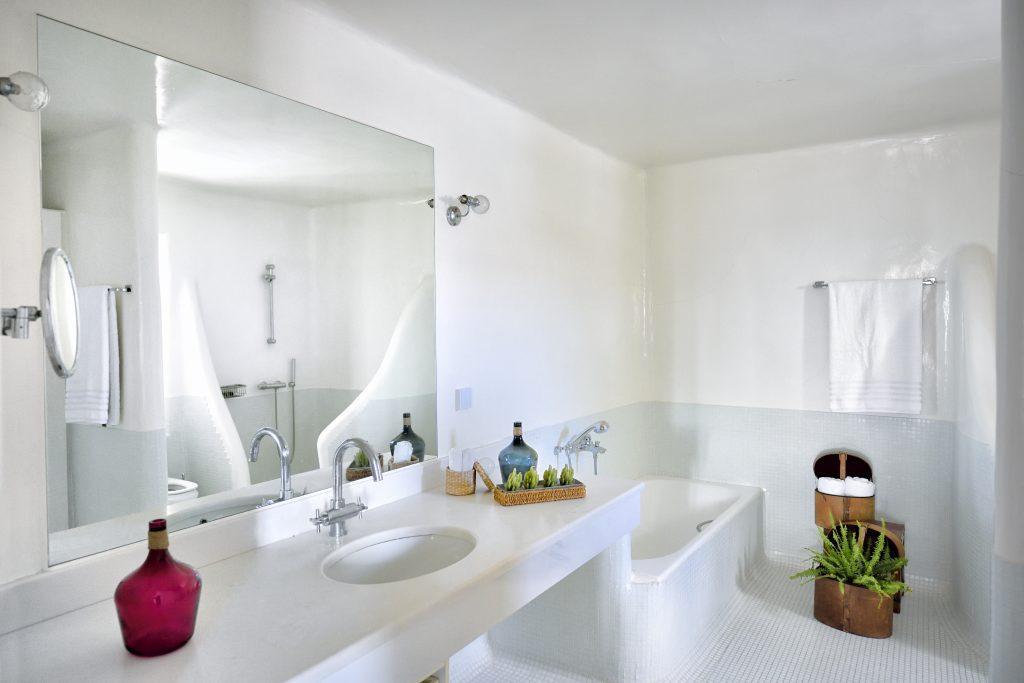 white bathroom walls with a large mirror and details of green decorative flowers