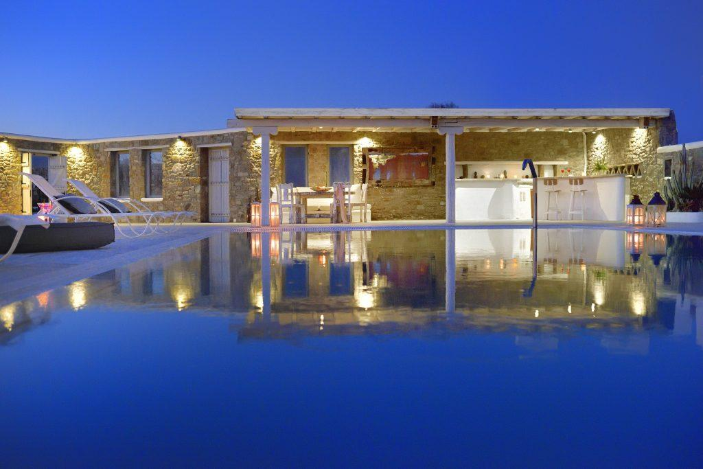 night view of the villa with stone walls that are dimly lit and white bar an ideal place for summer parties with friends