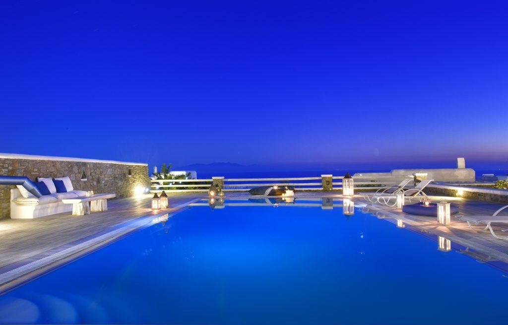 courtyard of the villa with a pool lit by lanterns and candles that contribute to the atmosphere on a pleasant summer night