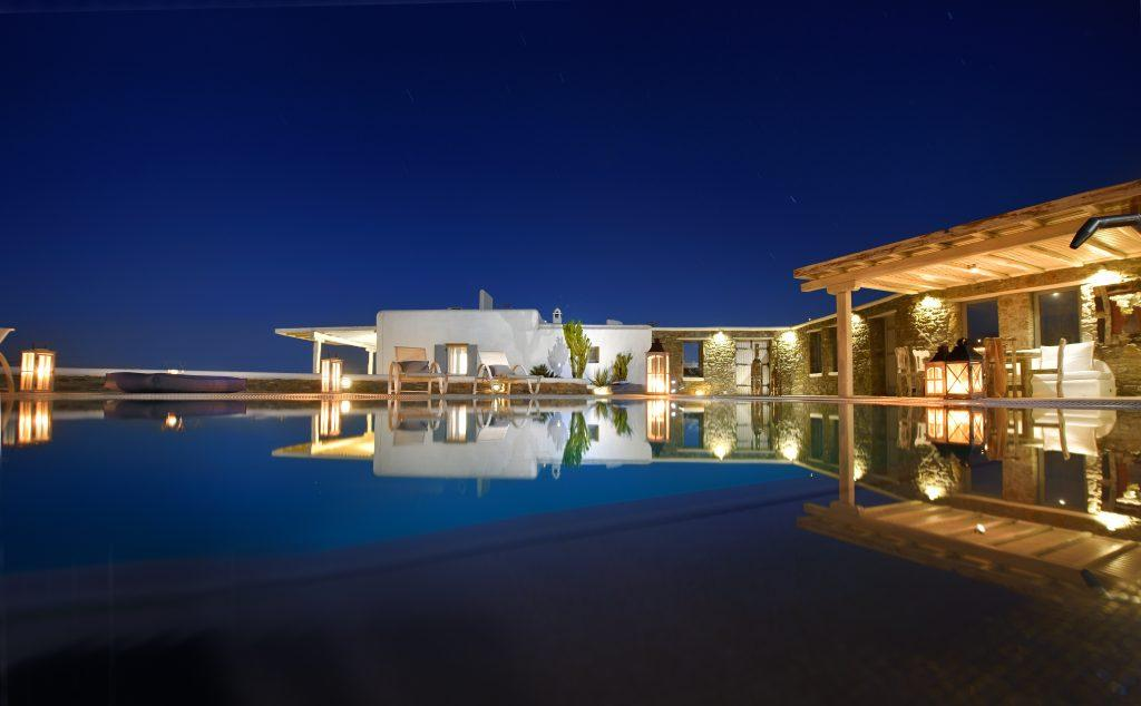 night view of the villa with stone walls and a wooden canopy from the infinity pool