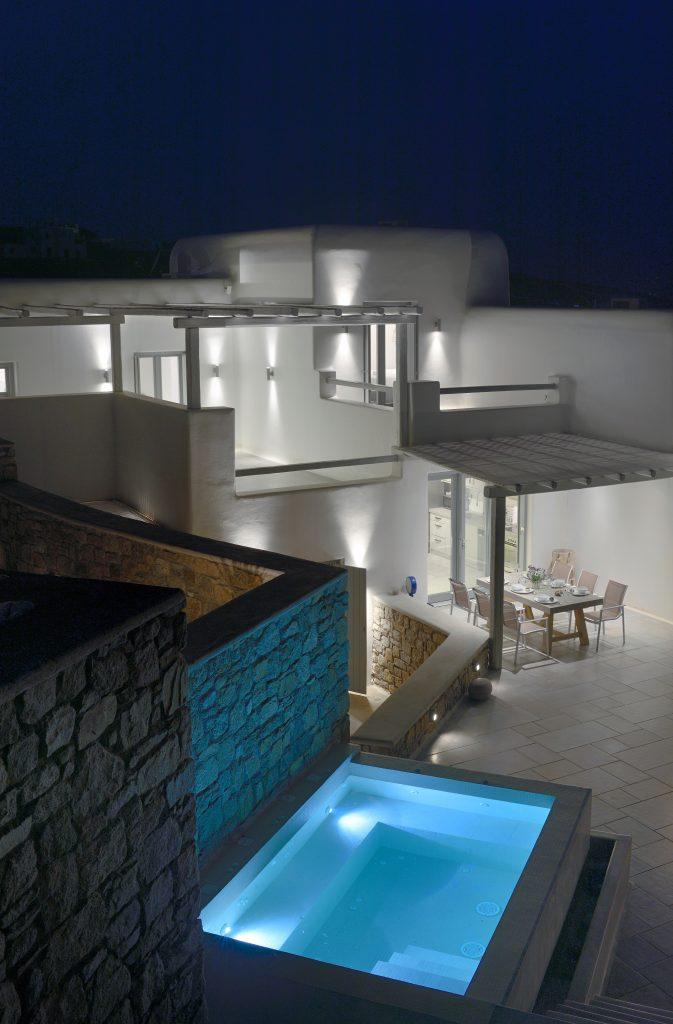 night view of a white villa with a lighted pool