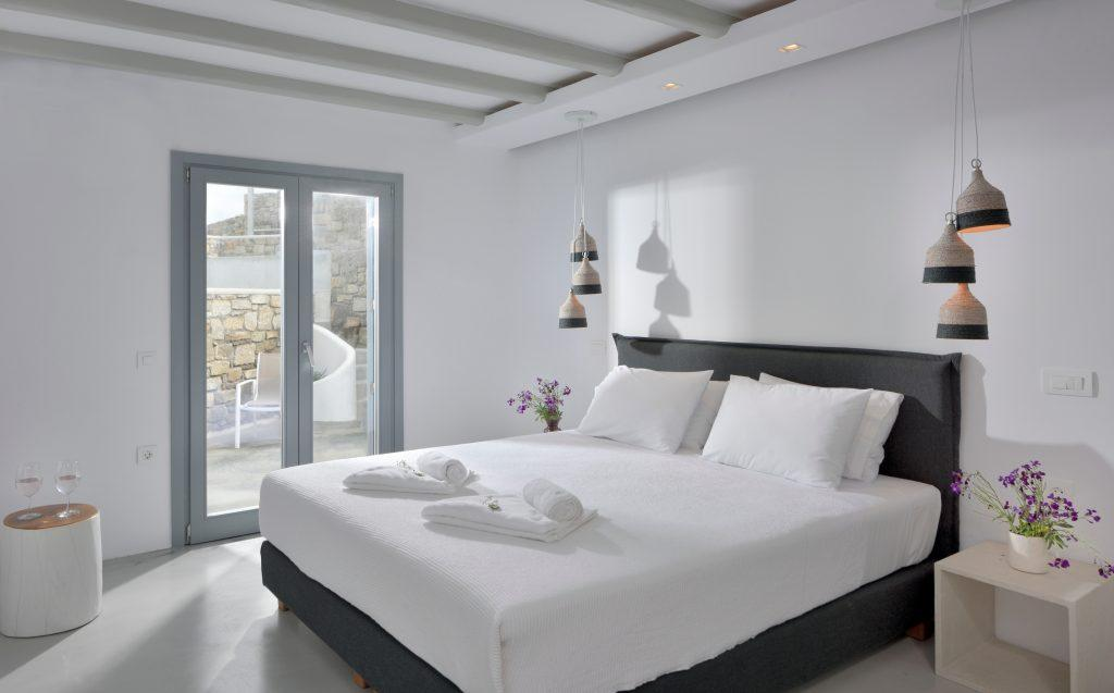 white walls of the room with a comfortable gray bed and a wooden bedside table decorated with flowers
