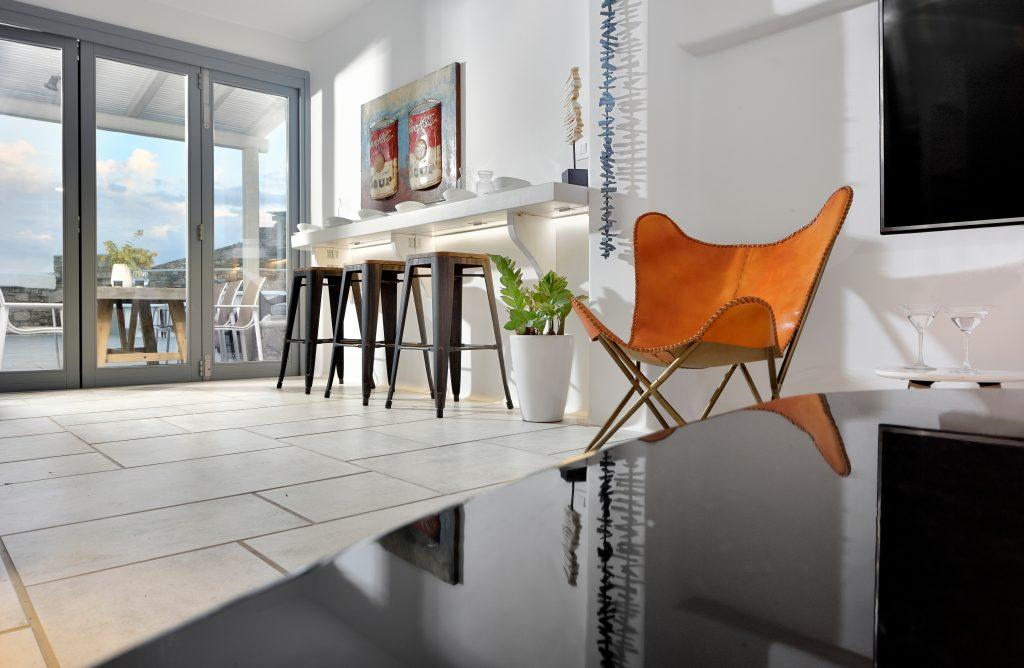 modern room with bar stools and a decorative comfortable armchair