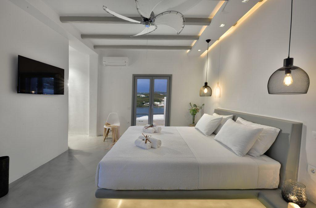bedroom white walls with comfortable gray king size bed and TV