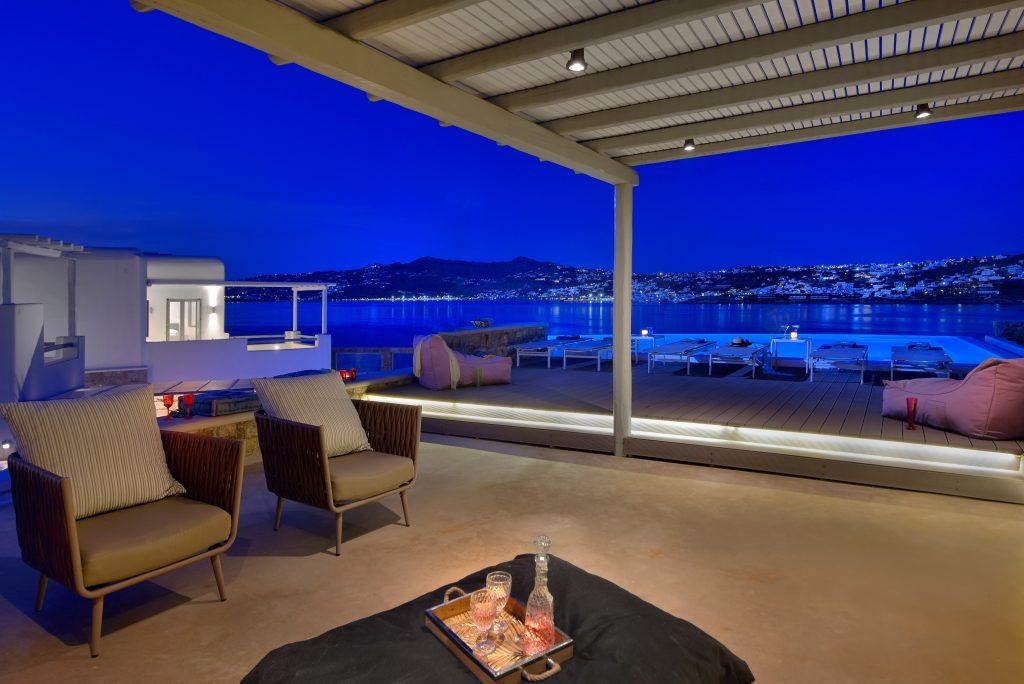 view of the starry sky above the sea from the courtyard of the villa with comfortable armchairs and a swimming pool