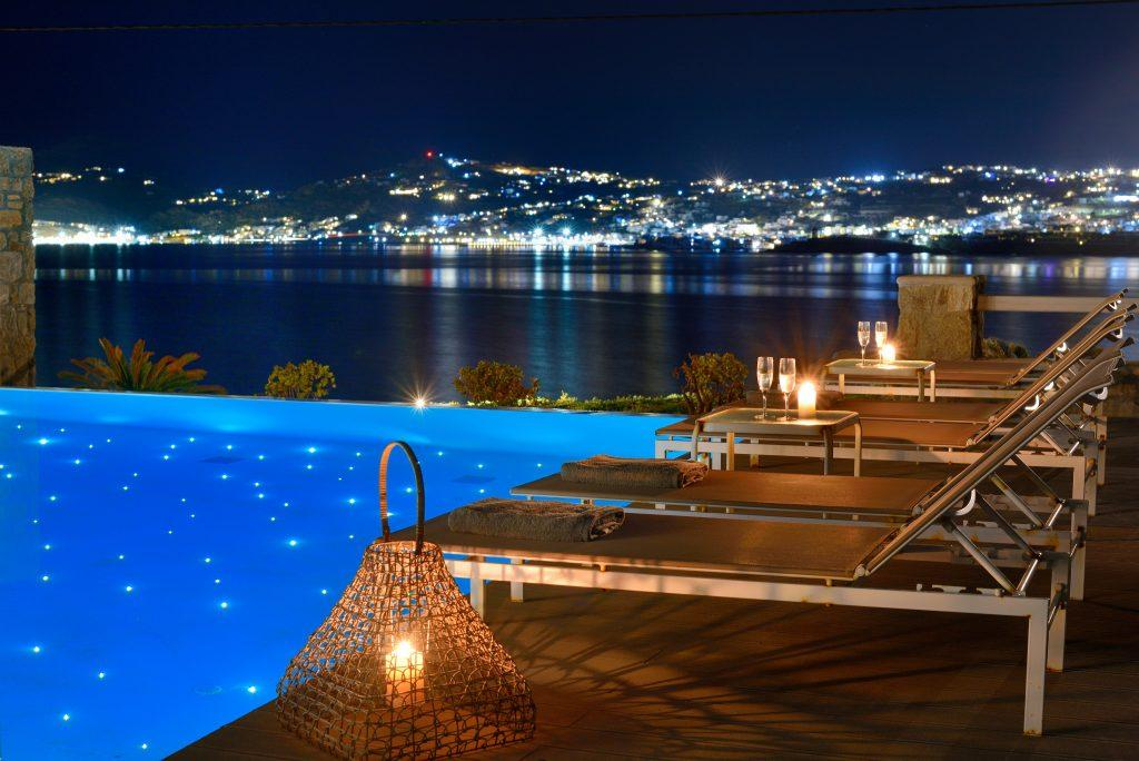 view of the illuminated city and the glistening sea from the illuminated pool ideal for a romantic night under the stars