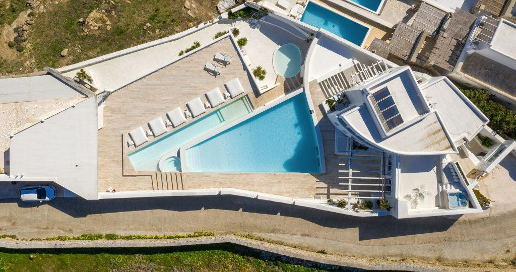 view of the villa with a spacious yard, swimming pool and separate parking