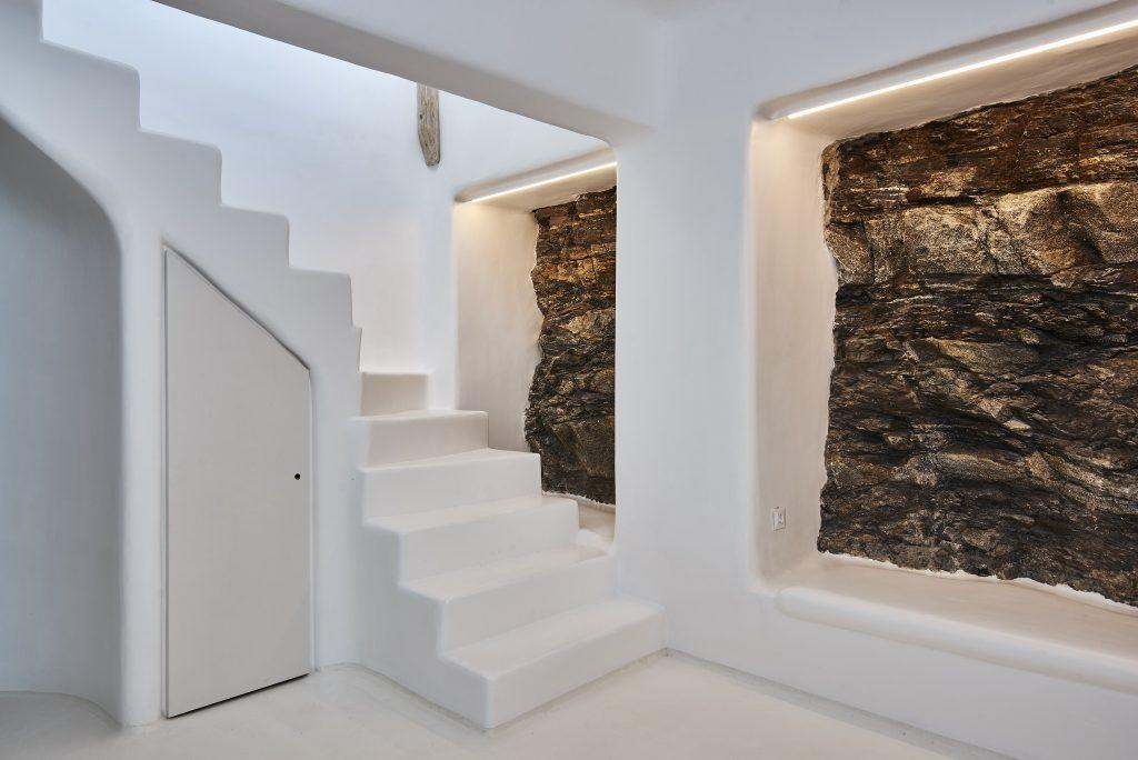 hallway with a mixture of white and stone walls and modern white stairs