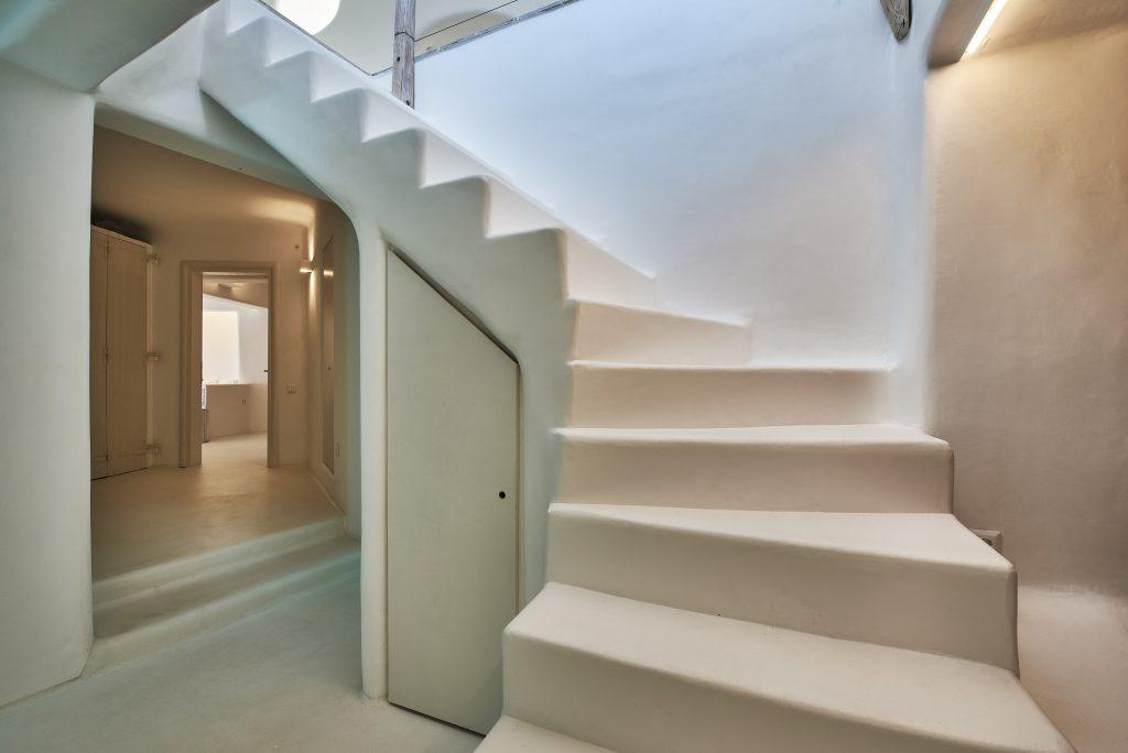 hallway with white walls and modern white stairs