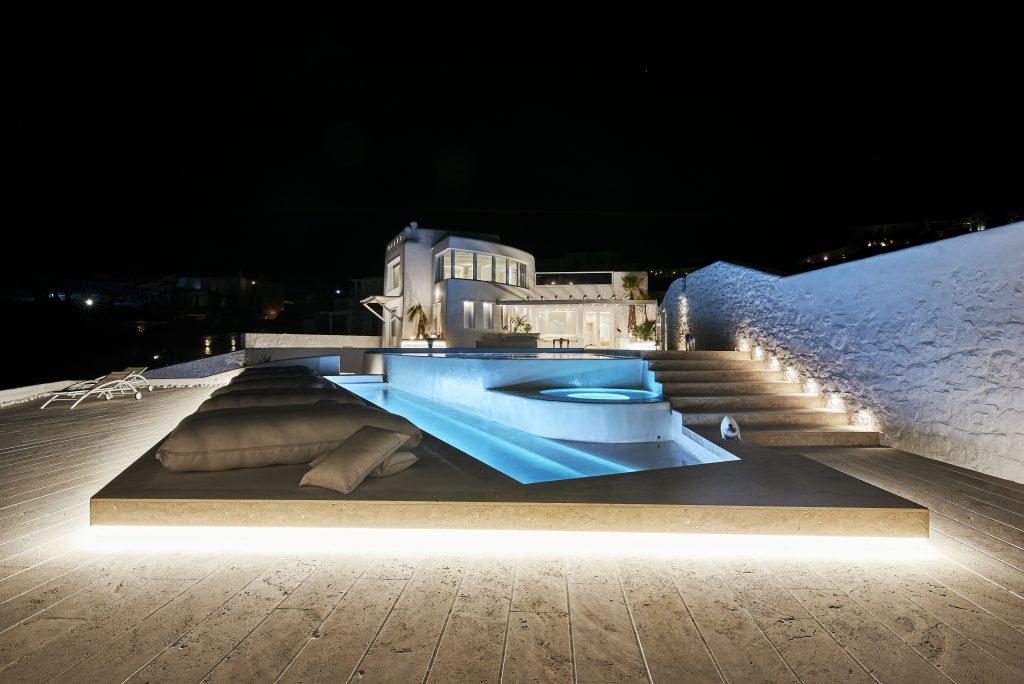 luxury villa with white steps lit by lamps leading to the pool and spacious courtyard