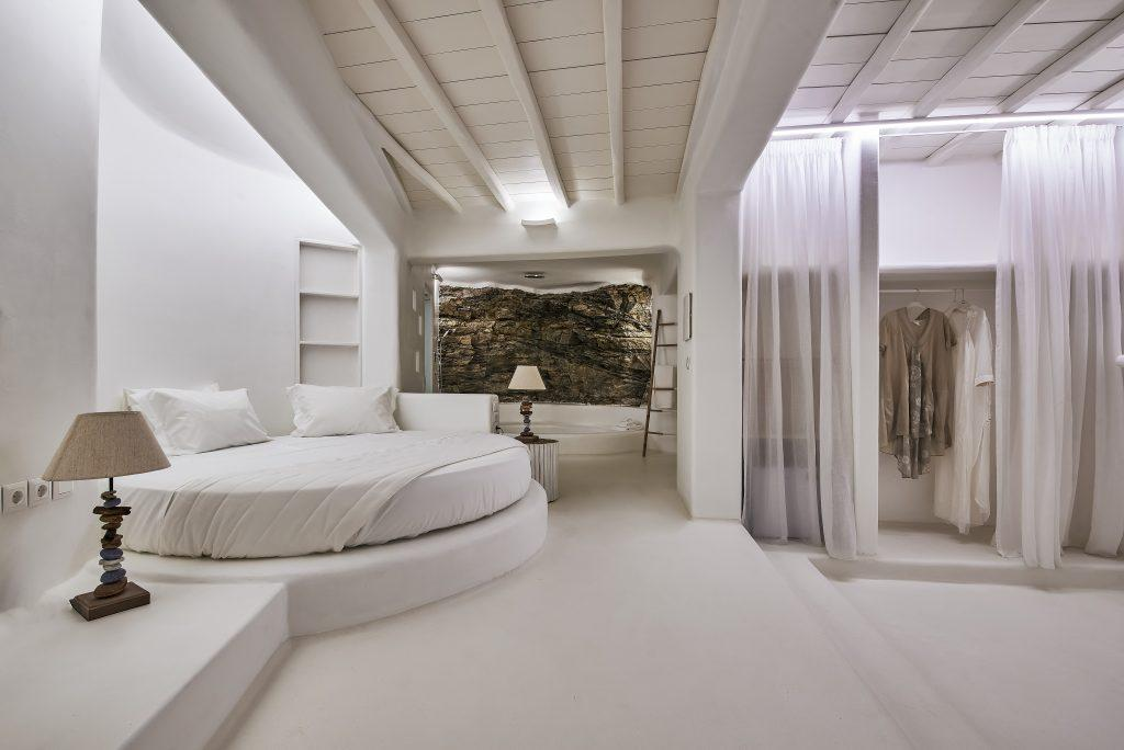 spacious bedroom with white walls and a comfortable round bed