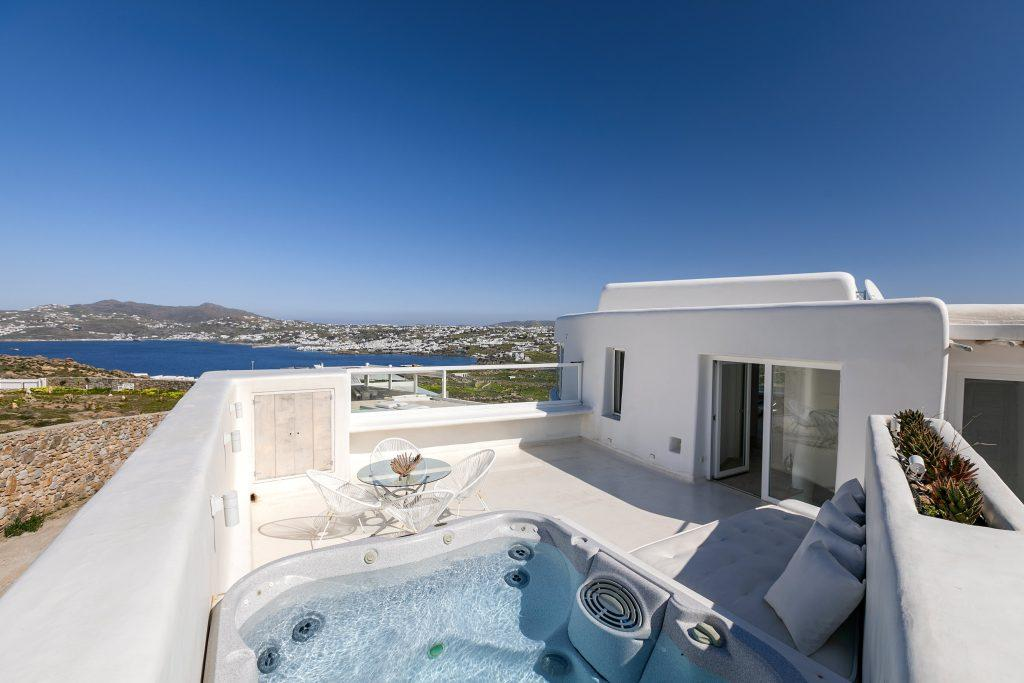 view of a luxurious white villa with a beautiful balcony