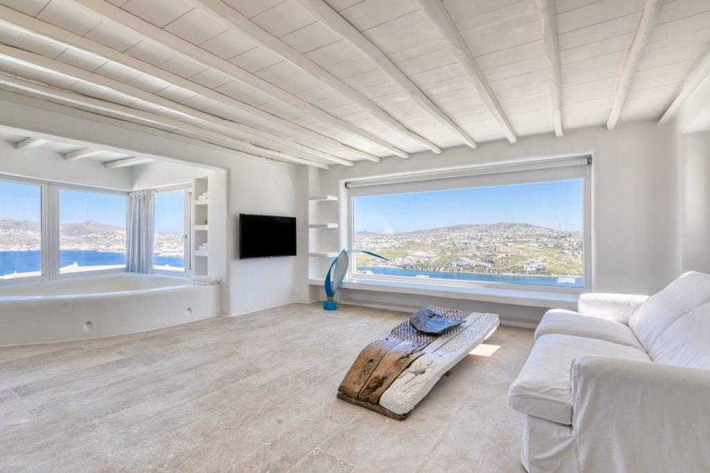large windows overlooking the crystal blue sea from a room with comfortable white furniture