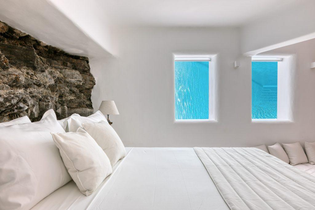 bedroom with double bed and specially designed stone wall that is lit