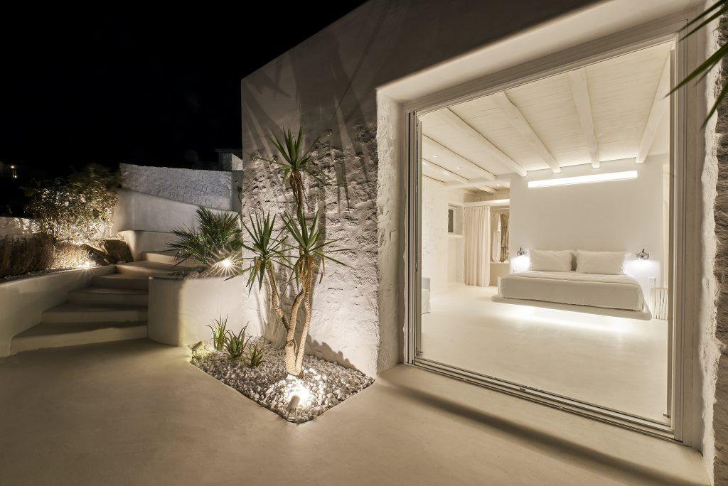 perfectly lit bedroom with a large bed and a view of the modern exterior of the villa