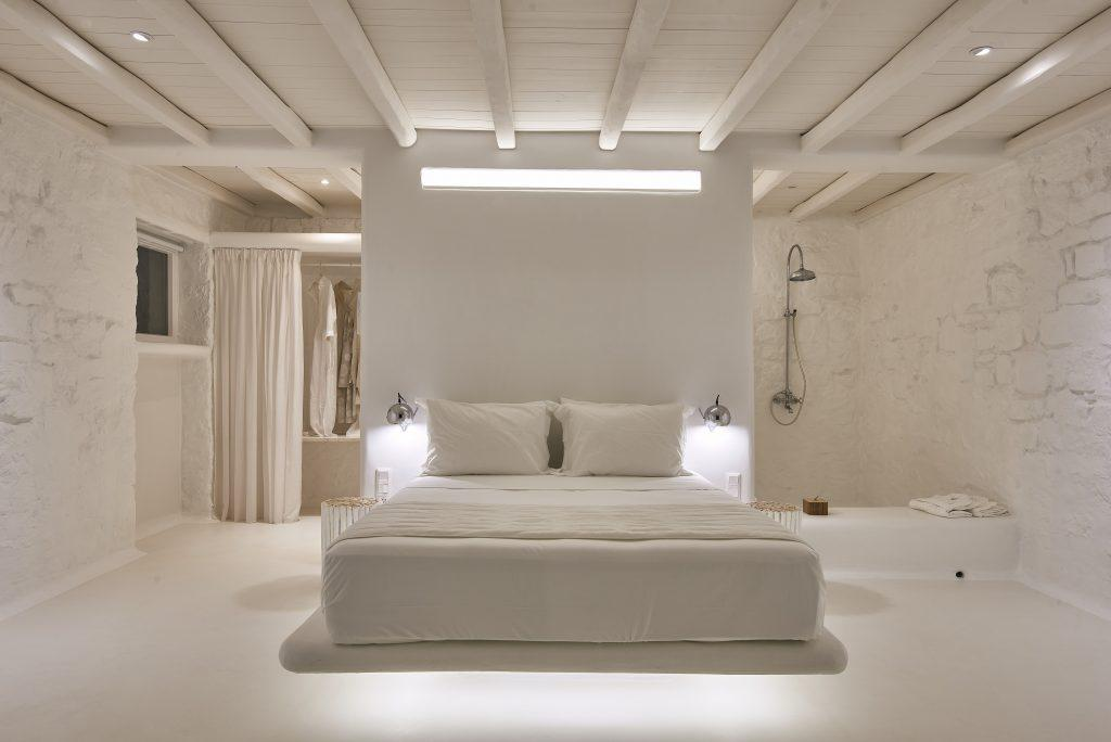 bedroom with comfortable king size bed lit by modern designed lamps