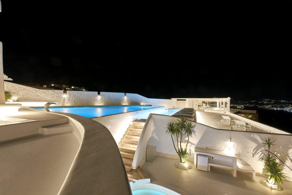 night view of the villa with two large lighted pools and a spacious courtyard
